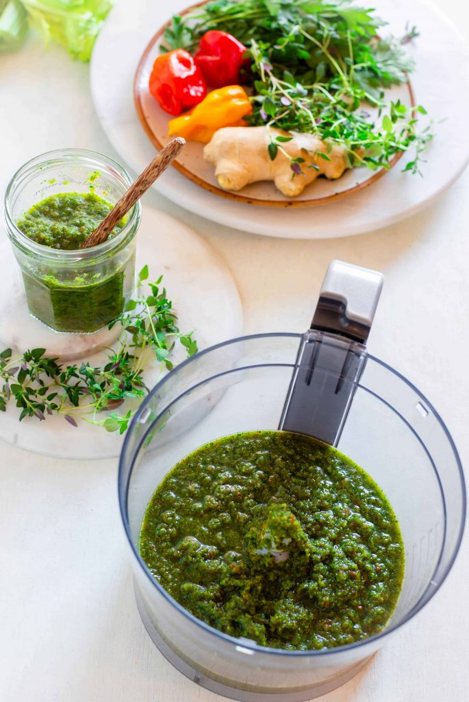 image of the blended Caribbean green seasoning in food processor and glass jar