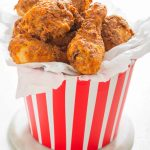 cooked kfc chicken in a takeaway paper bucket