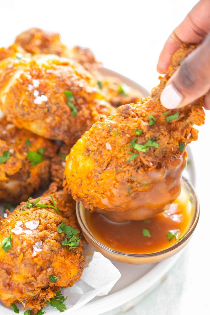 Dipping air fried chicken into gravy