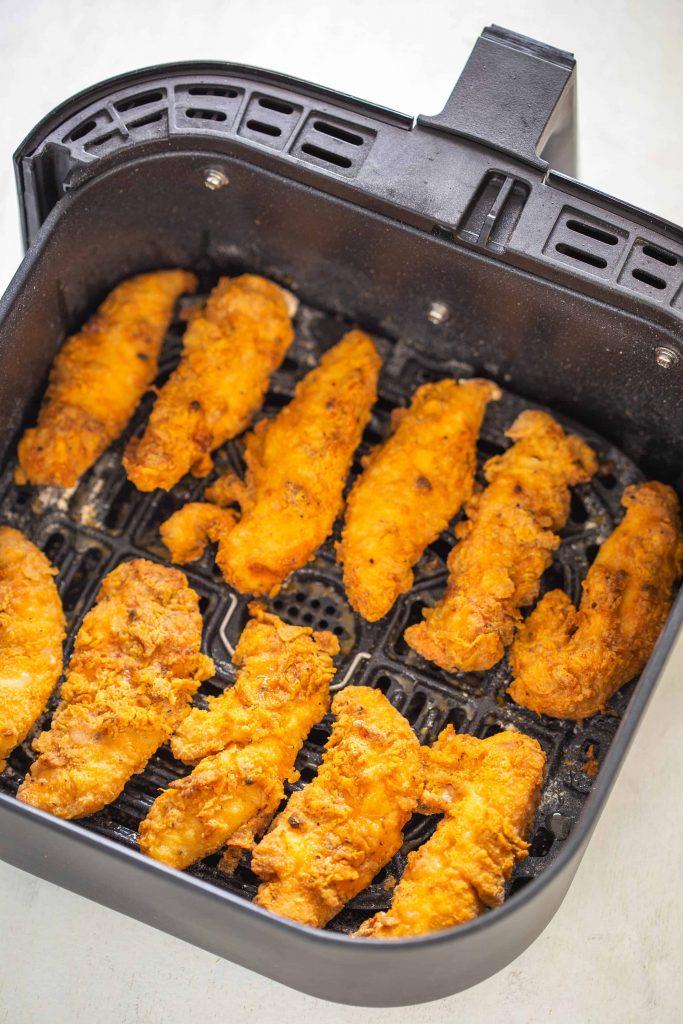 crispy cooked chicken tenders in an air fryer basket