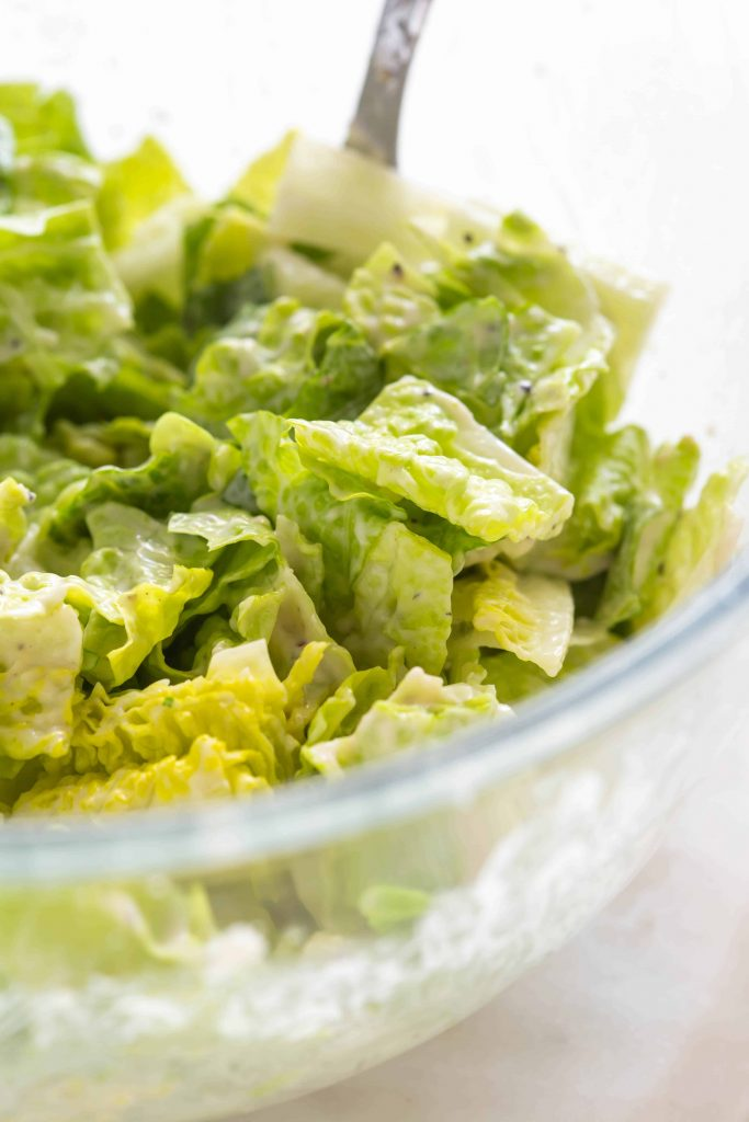 romaine lettuce in a bowl mixed with homemade caesar salad dressing
