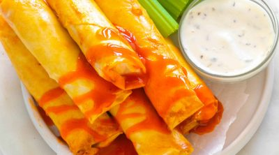 air fryer buffalo chicken rolls on a plate with a dip