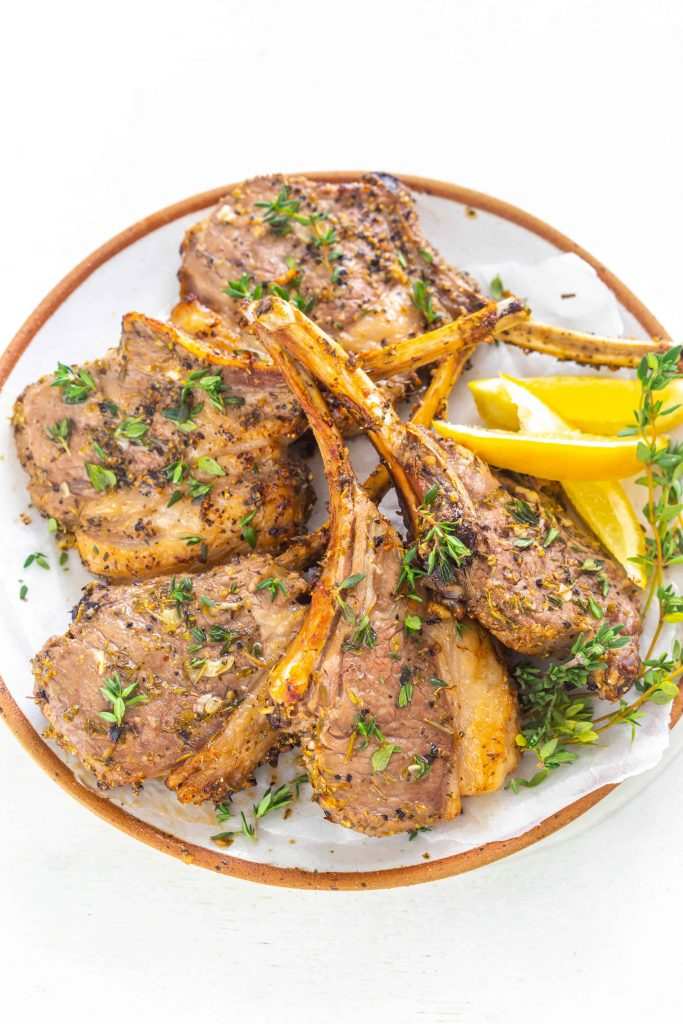 air fryer lamb chops on a plate with lemon wedges