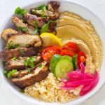 air fryer chicken shawarma in a bowl with salad rice and hummus